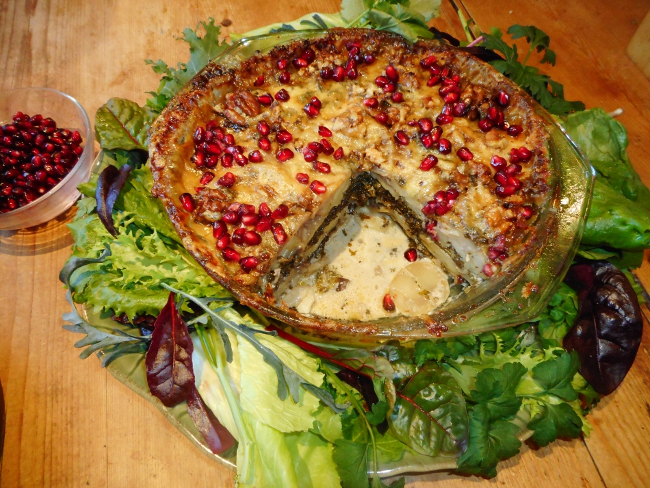 Potato, kale, Two Cheese and Walnut Bake - garnished with pomegranate seeds and surrounded by salad leaves